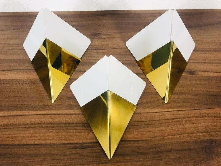 Amazing set of wall lamps by the Austrian brand Kalmar Franken made in the 1960s. Triangle white ice glasses which are stuck to the brass body.  The light requires one E14 light bulb.