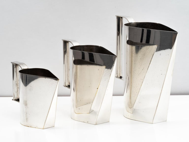 A unique and beautiful set of three Italian silver plated brass pitchers or carafes attributed to Cini Boeri from the mid-1970s. Expertly combining hard angles with soft curves, these elegant display pitchers work well as a grouping or individually.