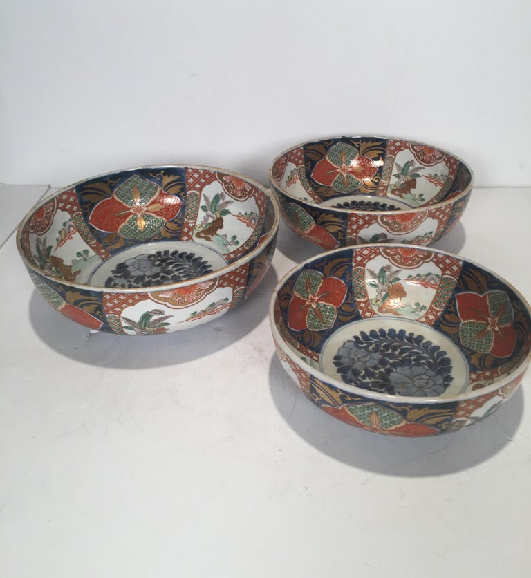 A rare set of three hand painted Imari porcelain graduated sized bowls with the same hand painted scenes and decoration on each. The large is 12 inches in diameter, with the medium 11 inches and the smallest 10 inches. Meiji period, circa 1880s.