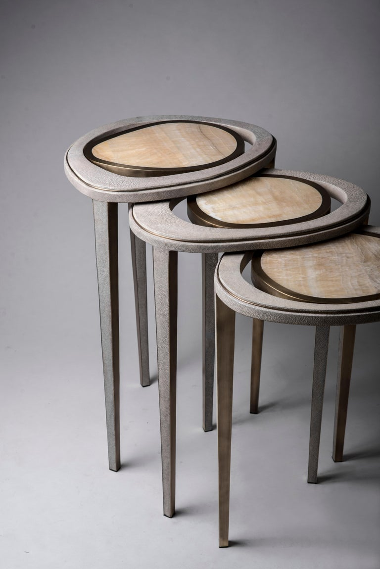 The set of 3 peacock nesting side tables are an iconic R&Y Augousti piece and one of their first designs. The piece is Minimalist and sculptural, with inspiration of course from the shape of exotic peacock feathers. The piece is inlaid in a mixture