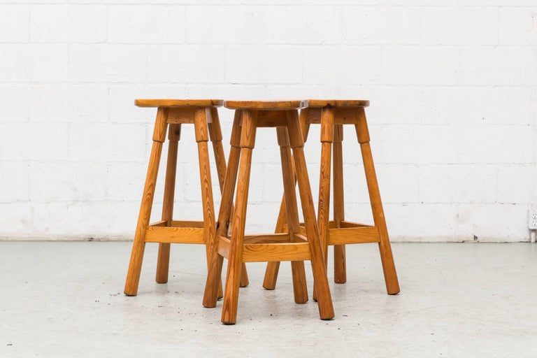 Set of three tall pine bar stools with pear shaped seats, footrests by Rainer Daumiller. Lightly refinished. Set price.