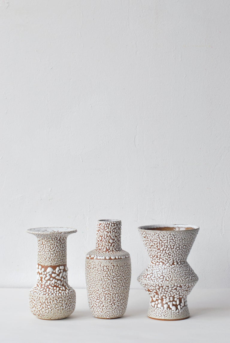 Set of 3 white stoneware vase by Moïo Studio. Dimensions: 17 x 9 x 9 cm  16 x 6 x 6 cm  17 x 7 x 7 cm Materials: White crawl glaze on tan stoneware  Is the Berlin-based ceramic art studio of French-Palestinian artist Maia Beyrouti. It was