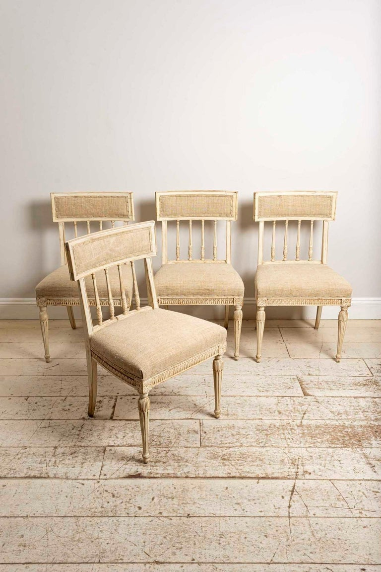 Set of 4 1920s hand painted dining chairs reupholstered in a coarse neutral French linen fabric.