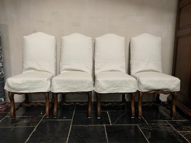 A set of 4 19th century walnut French chairs. This Louis XIV model is also known as Os de Mouton or 'Sheepclaw feet'. The wood is pegged and maualy joined and turned by hand. It has a good patina and very solid. All have a custom made losse linnen