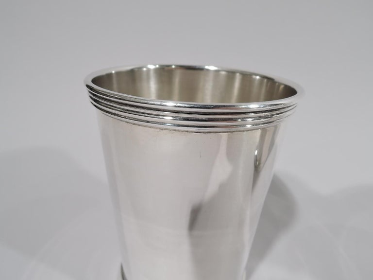 Set of 4 sterling silver mint juleps. Made by Wm Rogers Mfg Co. (part of International) in Hartford. Each: Straight and tapering sides, and reeded rim and base. A quartet of cups for a select Derby Day celebration. Fully marked. Two cups numbered
