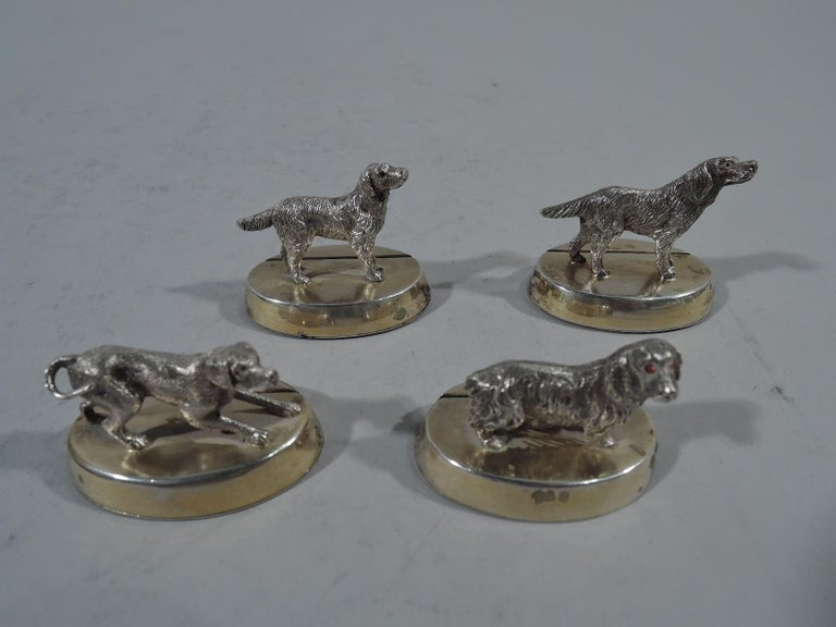 """Set of 4 George V sterling silver place card holders. Made by Sibray Hall in London in 1922. Each: Cast canine figure mounted to oval gilt-washed base with slit. A canine medley. Each dog different as they are in real life. For a special """"pack"""""""