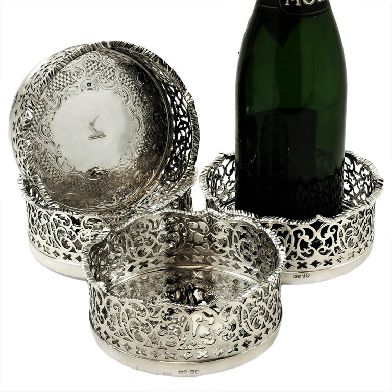 A magnificent set of four Antique Solid Silver Bottle Coasters. Each Coaster has a tall, ornate pierced sides with a shaped rim. The interior of each Coaster is decorated with a delicate complementary engraved design around an engraved crest. These