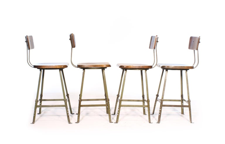 Authentic set of four vintage Industrial factory / shop stools. Feature adjustable steel bases, formed solid wooden seat and solid wood height adjustable backrest. Stools have been cleaned and checked for stability, and adjusted to their maximum