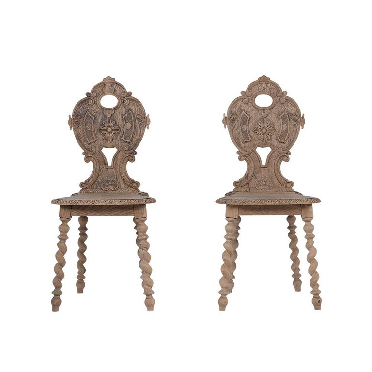This Set of Four Baroque Side Chairs are in good condition and made out of oakwood with a bleached wood finish. The chairs have elegantly hand carved backrest, intricate molding along the edges of the seats, and rest on sturdy spiral column legs.