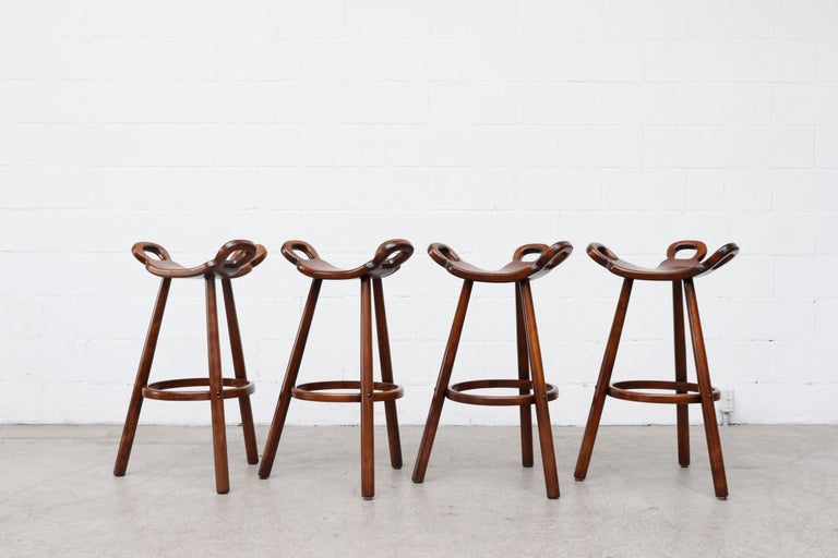 Set of 4 Sergio Rodrigues style Brutalist 'Marbella' bar stools by Confonorm. Organically carved seating and reverse tapered legs with wood footrests. Similar styles available with metal footrests. Listed separately. Set price.