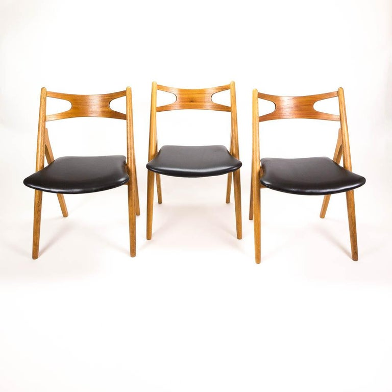 Excellent set of 4 oak and teak framed CH29 sawbuck dining chairs with new black leather upholstered seats. Designed by Hans Wegner in the 1950s and made by Carl Hansen & Søn, Denmark, 1960s.