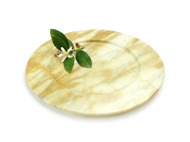Set of 4 hand carved charger plates from Yellow Siena marble. Multiple use as charger plates, plates, platters and placers. Dimensions: D 33, H 1.9 cm.