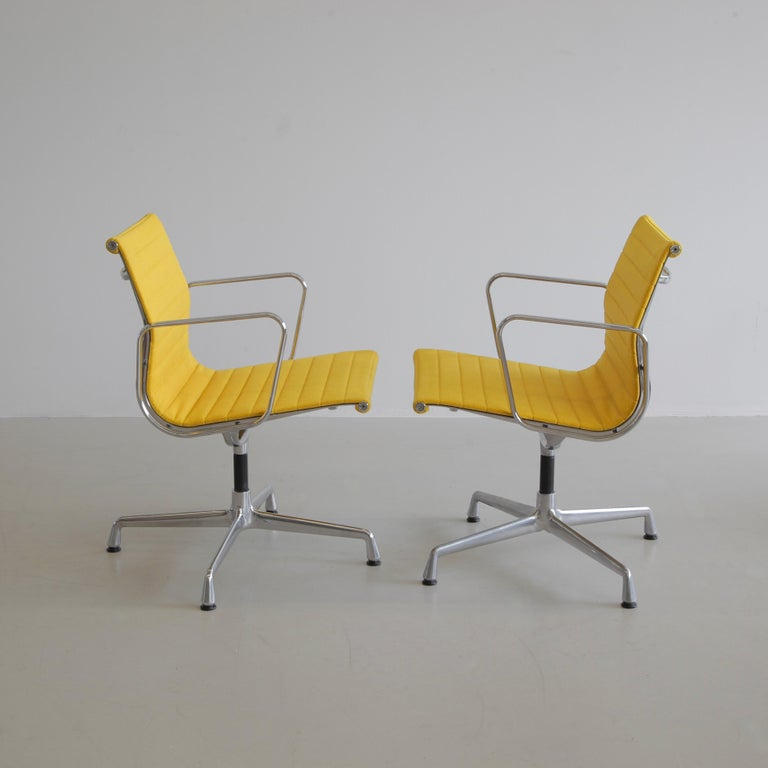 Aluminium office chairs designed by Charles and Ray Eames. Germany, VITRA, dates vary on the base.  A beautiful set of yellow hopsack and chromed aluminium rotating chairs with armrests. Best colour ever!