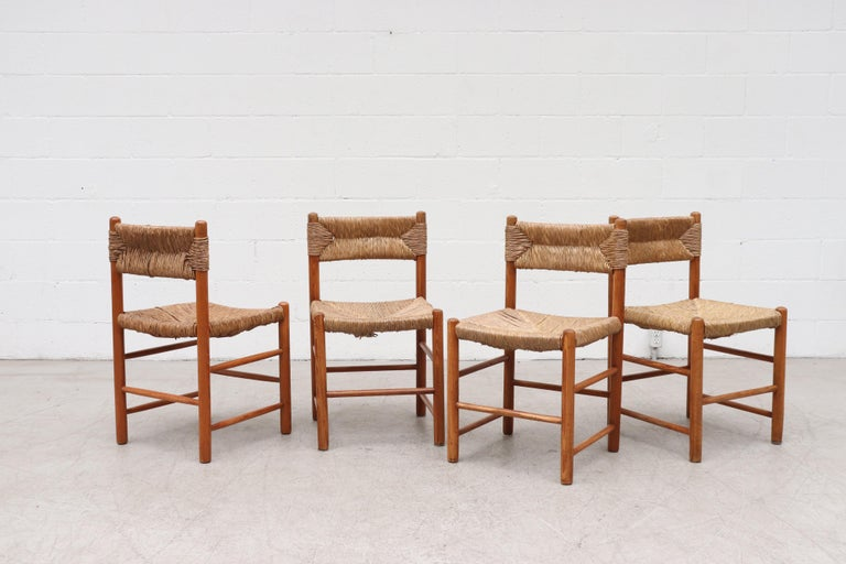 Set of 4 Charlotte Perriand Style Pine and Rush Dining Chairs. Lightly Refinished Pine Frames with Original Woven Rush Seat and Back Rest. In Very Original Condition with Visible Wear, Visible Breakage of Rush and Patina to Wood. Two Sets Available,