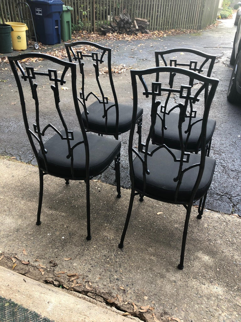 Set of 4 chic black painted iron patio chairs having a stylish chinoiserie silhouette. Upholstered seats are Sunbrella, but a bit tired. Priced accordingly.