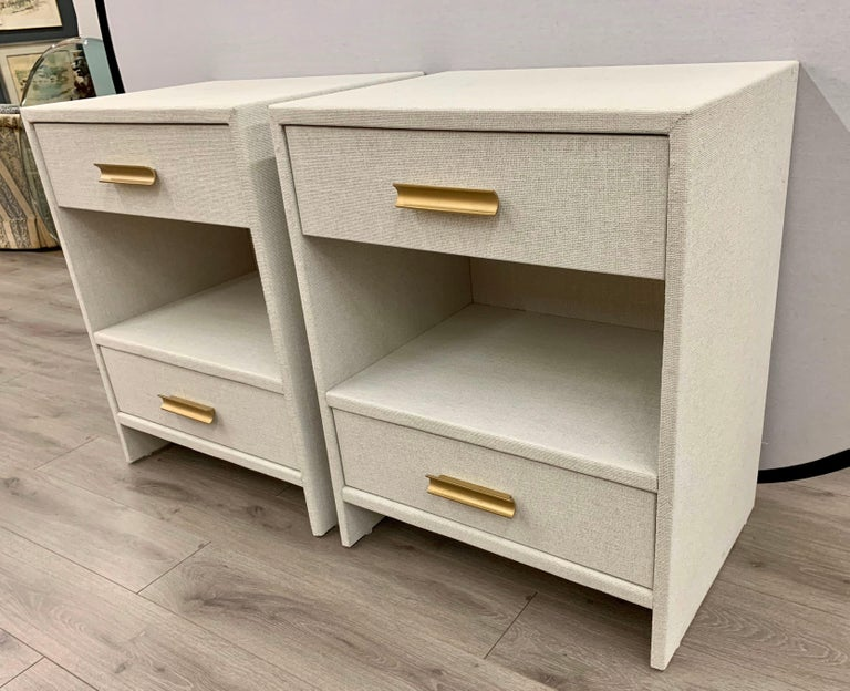 Sleek, simple lines give these nightstands a Mid-Century Modern feel and are wrapped by hand in fine linen then given a multi-layered paint glaze in a neutral oyster color. They have two drawers with a center shelf. Brass handles give it a