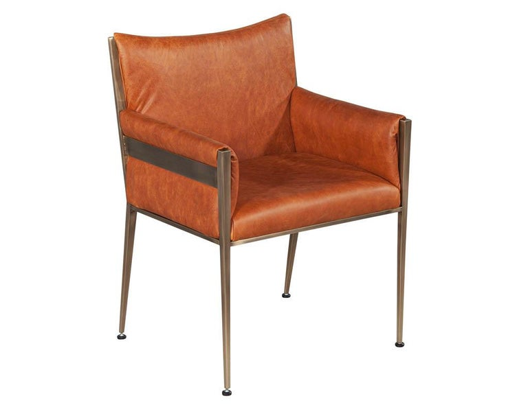 Set of 4 custom modern leather dining chairs cognac leather. Custom made by Carrocel. Finished in a butter soft natural Italian cognac leather and aged brass finish.  Price includes complimentary scheduled curb side delivery service to the
