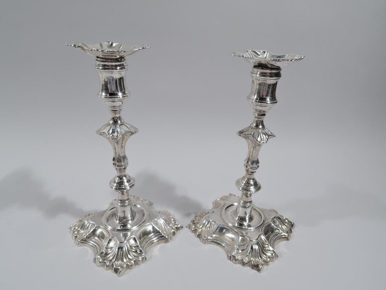 Set of 4 George II cast sterling silver candlesticks. Made by John Cafe in London in 1748. Each: Knopped shaft with leaf flange mounted to inset circle in scroll and leaf quadrilateral foot. Spool socket. Bobeche lobed detachable with leaf corners.