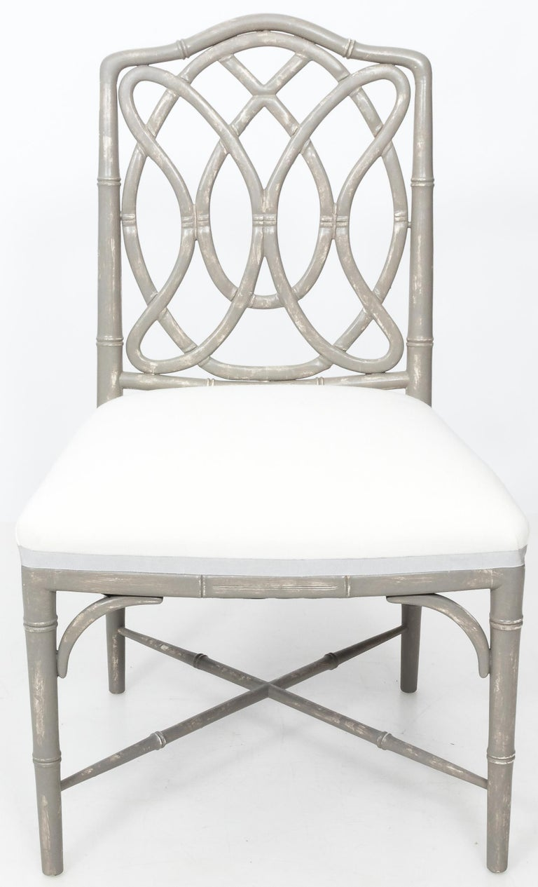 Set of 4 faux bamboo dining chairs. Loop back design. Newly refinished in antique gray painted finish. Newly upholstered in white linen with gray tape trim.