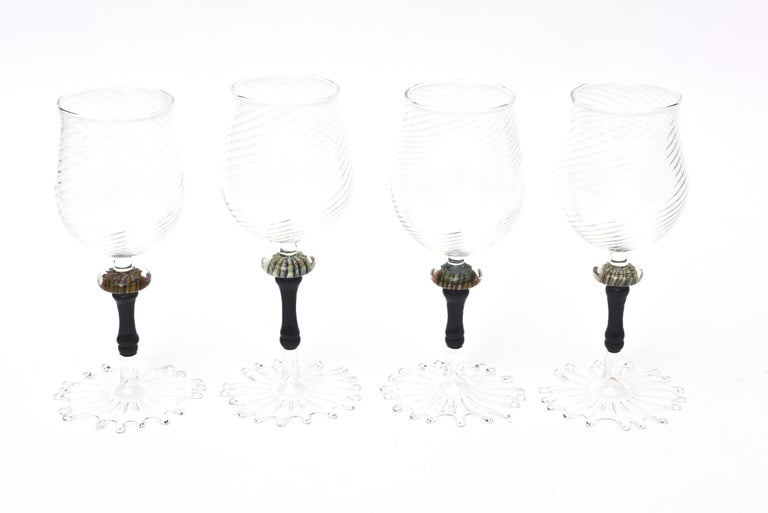 These stunning and unusual set of 4 large hand blown Murano wine goblets are from 2008 and are signed but illegible to read. They say a name and 08. They have an exaggerated web base at the bottom and in the center is amber and gold aventurine with