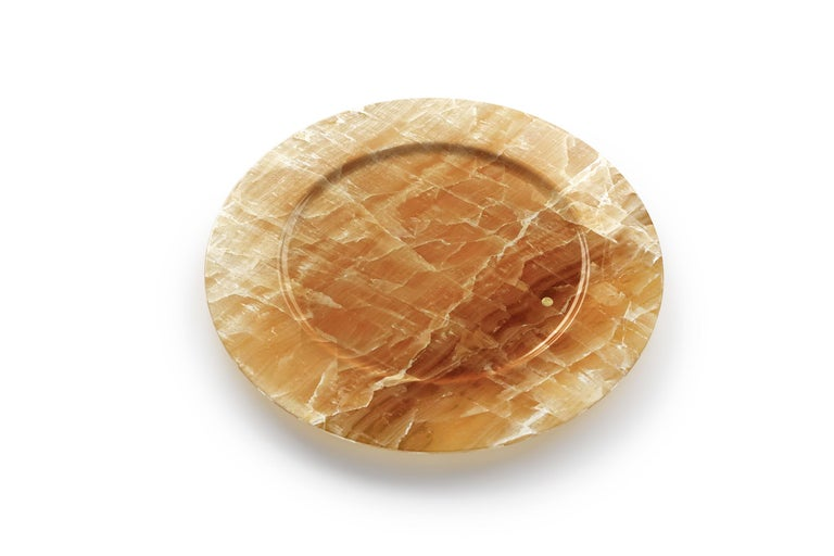 Set of 4 hand carved charger plates from Amber onyx. Multiple use as charger plates, plates, platters and placers. The polished finishing underlines the transparency of the onyx making this a very precious object. Dimensions: D 33, H 1.9