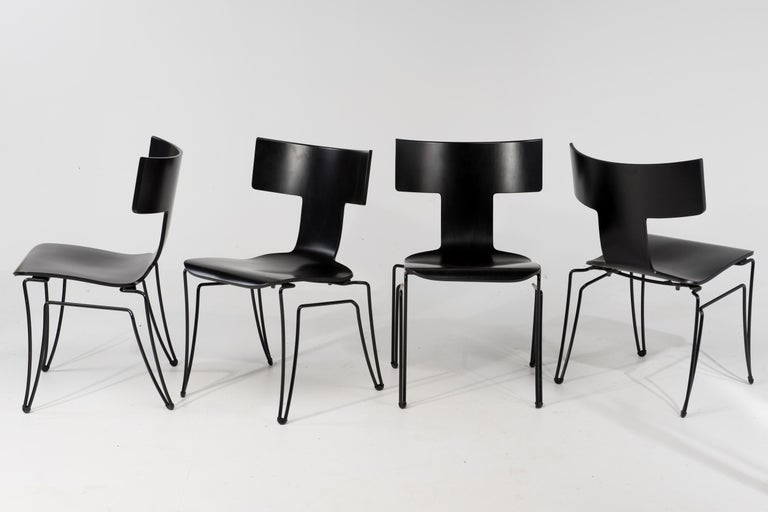 Set of 4 iconic klismos style Anziano chairs produced by Donghia in the 1980s and designed by John Hutton, having black coated steel wire structure and molded beechwood veneer. Chairs are stackable. Finish is not solid or opaque but subtly shows the