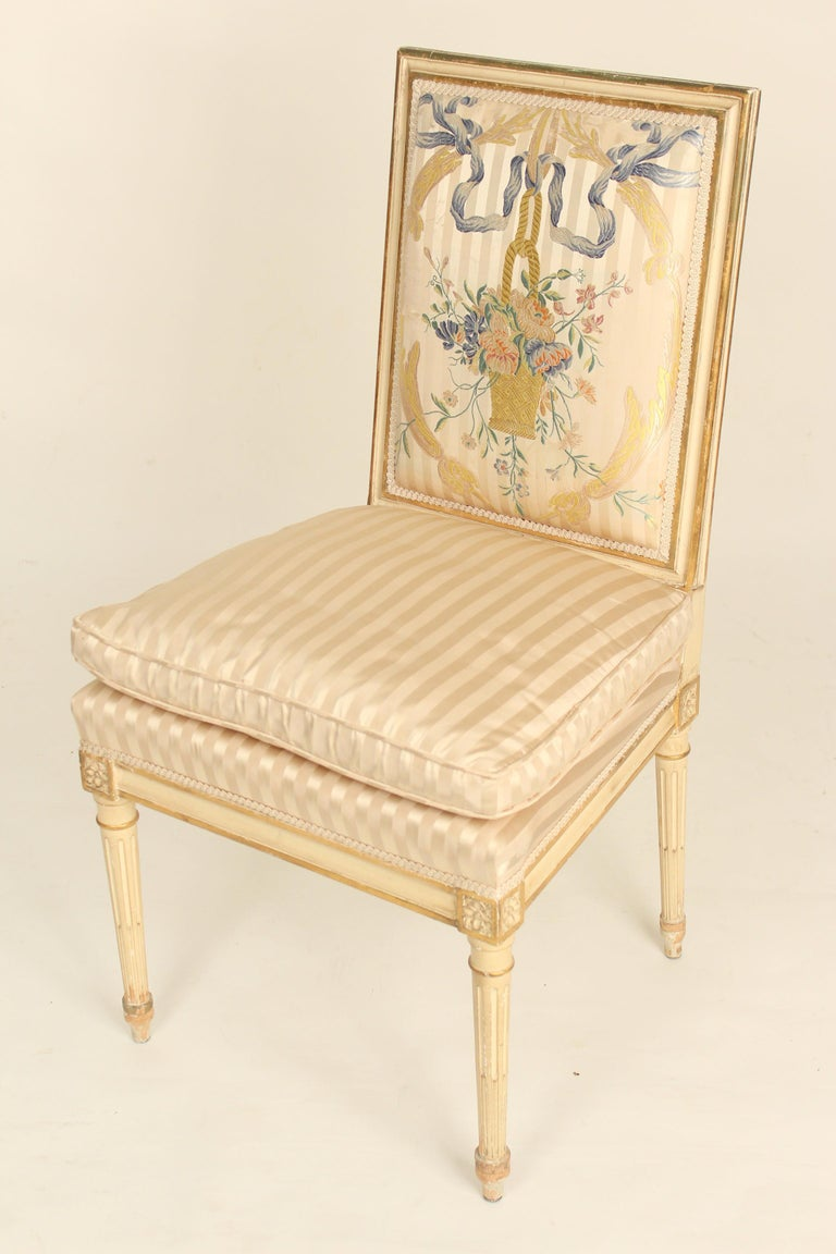 Set of 4 Louis XVI style painted and partial gilt side chairs with silk upholstered seats and silk embroidered backs, circa 1960s.