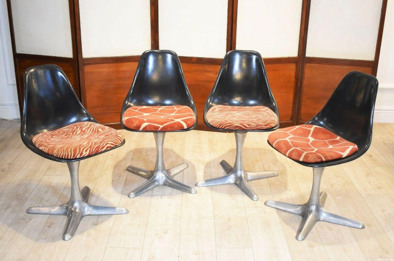 Set of 4 mid-20th century dining chairs designed by Maurice Burke for Arkana  In their original animal print seat cushions. The chairs comprise of a black plastic shell and set on aluminium bases with swivel mechanism.  Iconic space age design,