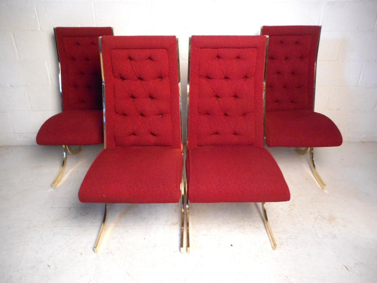 This impressive set of midcentury dining chairs feature beautiful red vintage upholstery covering a tufted backrest and plush seating. The brass-plated base employs an interesting design which enhances the chairs' unique visual profile. An