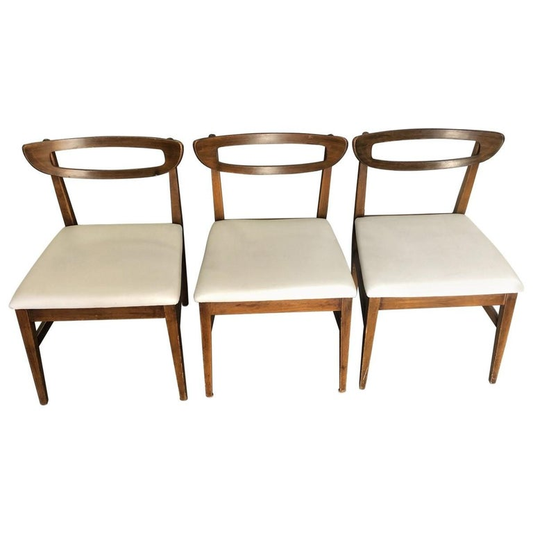 Sleek and shapely, this eye-catching set of four plywood dining chairs includes three side chairs and one armchair. Rounded open top rails and white vinyl seats give these Mid-Century Modern dining chairs added sophistication.
