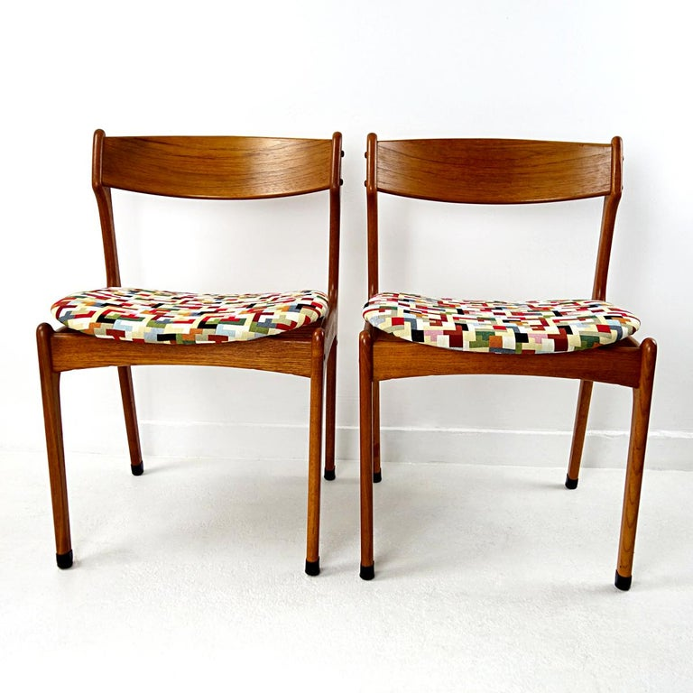 These very elegantly designed dining chairs are made of teak wood. They have some eye-catching details such as the visually floating seats, the protective feet covers and the visual wood connections. They have been reupholstered with a colorful yet