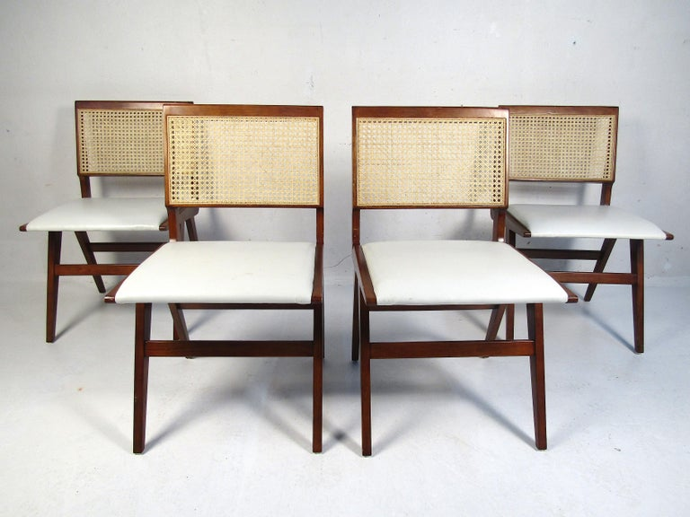 Set of 4 midcentury style dining chairs. Sleek angular frames with woven cane backs. Seats are covered in a white faux-leather upholstery.