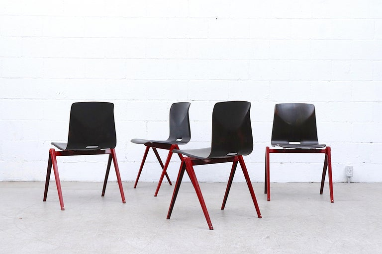 Set of 4 midcentury Prouve style stacking chairs with dark red enameled metal legs and Wenge toned bent ply-laminate shell seat. In original condition with some frame wear and visible scratching on seat. Wear is consistent with their age and use.