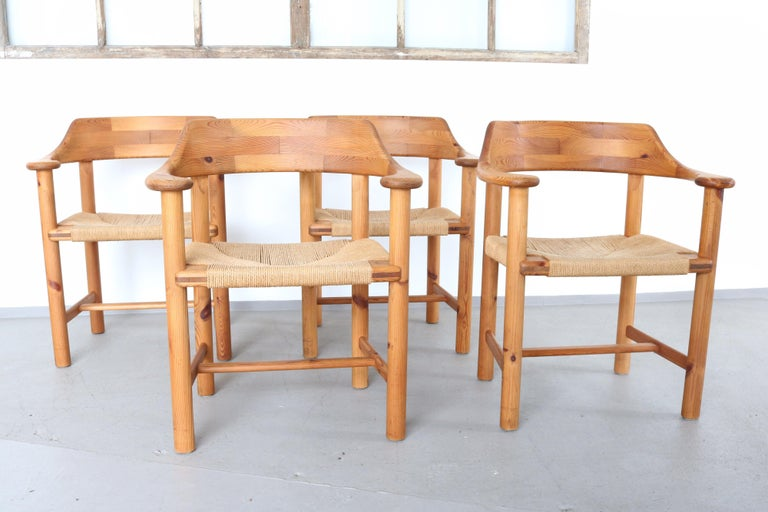 Fully original Rainer Daumiller Set of four armchairs with papercord seats and solid pinewood frame. Some of the seats have stains, but the overall condition is absolute authentic. The wood was cleaned professional. There is a matching table