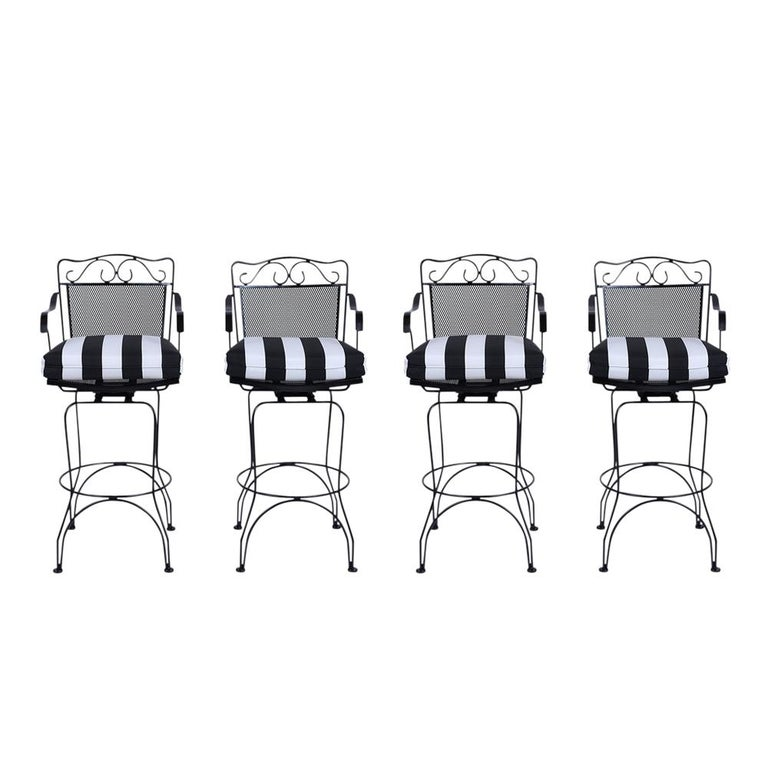This set of 4 vintage swivel bar stools are made from sturdy wrought iron that has been newly painted in a black finish. The set features a supportive low backrest and new upholstered black and white striped seat cushions with new foam inserts. The