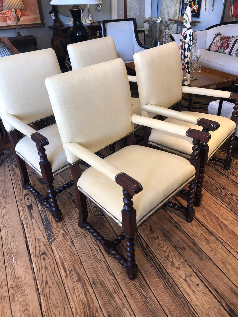Classic set of 4 Tudor style mahogany armchairs having pale yellow silk upholstery, barley twist arm supports, legs and stretchers and brass nailhead trim. Comfortable and solid chairs, but could use updated upholstery. Great as large dining