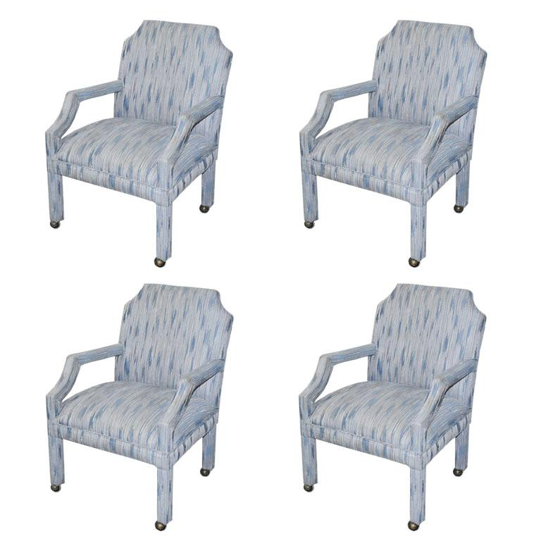 A set of four upholstered rolling chairs with chinoiserie inspired scalloped backs. A mix of Mid-Century Modern and Hollywood Regency, this set of chairs is upholstered in a cool blue flame stitch fabric. The arms are in a geometric shape with