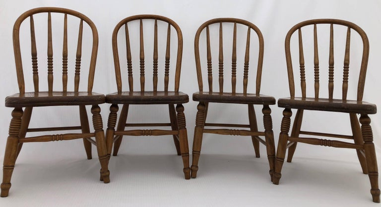 This set of four wooden children's chairs are lovely. They are solid and have spindle, rounded backrests. They are beautiful seats in a great patina and could be used for children to use or as a decorative element.