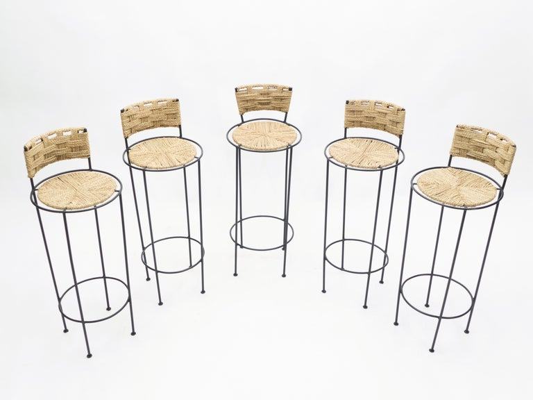 Beautiful patina is evident along the abaca rope seating and backrest of this set of five bar stools by Adrien Audoux et Frida Minet, giving away their vintage status. This natural style is typical of the French design of Audoux-Minet. Timeless
