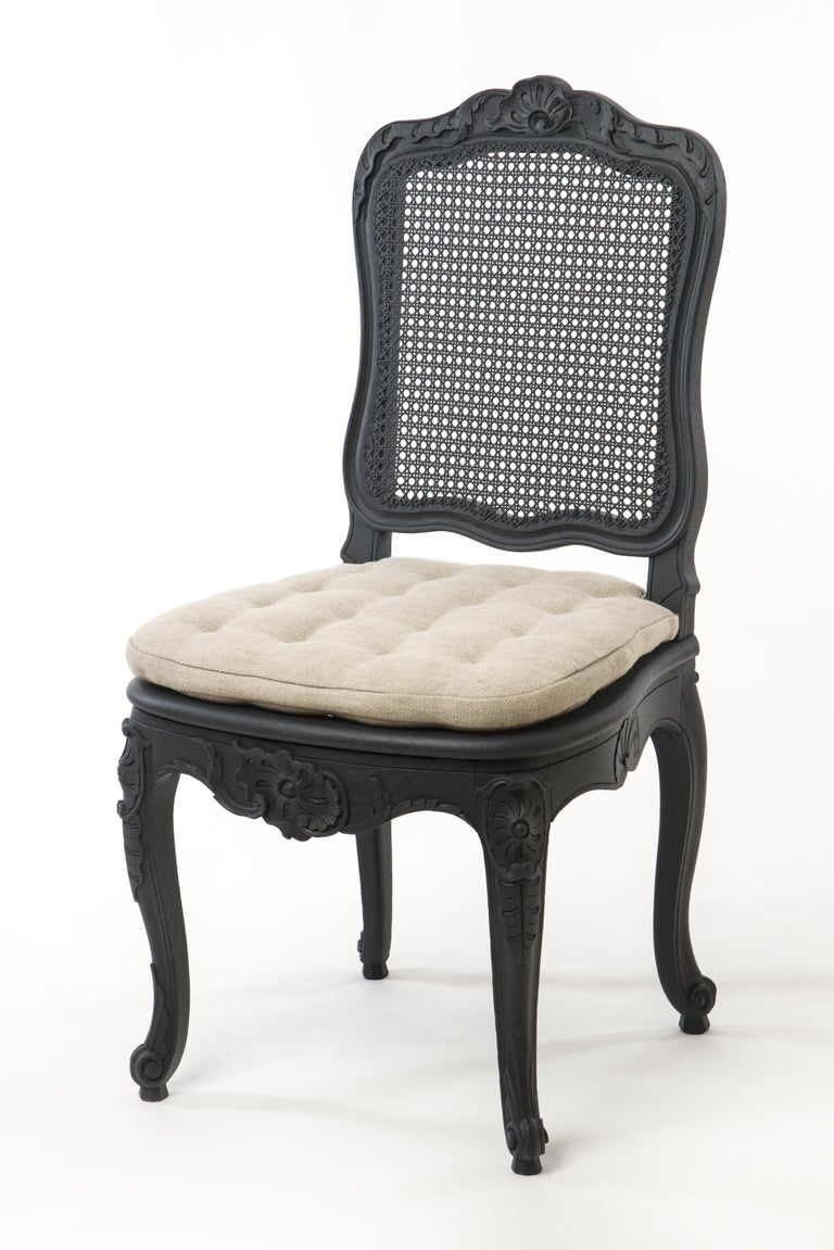 This set of 5 beautiful chairs in the Gustavian style come in an elegant black paint. The slightly curved legs as well as the seating frame and backrest feature sophisticated wood carvings that are truly setting these chairs apart. The wicker on