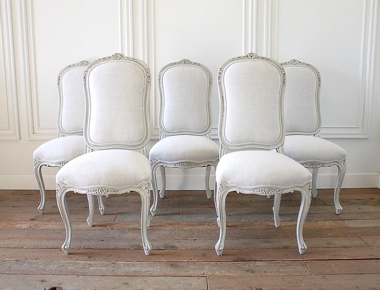 Set of 5 painted and upholstered dining room chairs in Belgian Linen 20th century Louis XV style dining chairs, upholstered in natural linen, with double welt trim. Beautiful carved flowers at the top and front seat with curved cabriole legs. Very