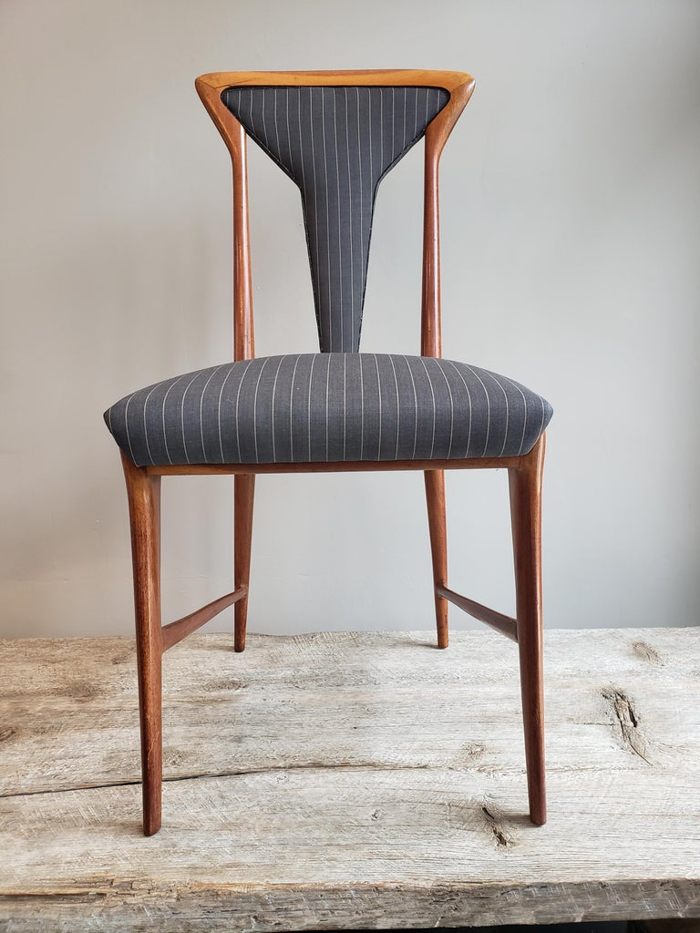 A set of 6 Mid-Century Modern upholstered dining chairs from Italy and designed by Carlo De Carli. Made out of walnut wood and upholstered in a sophisticated masculine gray and white pin striped fabric. Circa 1950's.