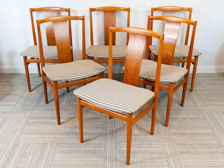 A set of 6 Danish teak dining chairs. Designed by Sorensen Henning and manufactured by Danex in the 1960s. The chairs have a single wide panel to support the back whilst sitting during long dinner parties. The chairs have been beautifully sculpted