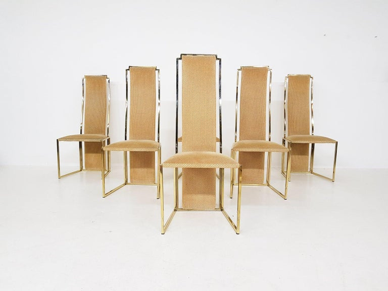 High-end gold-plated metal high back dining chairs by Alain Delon. Made and designed in France in the 1980s.  A set of six dining chairs made of gold plated metal and fabric. The chairs have fantastic geometric shapes and look classic and yet very