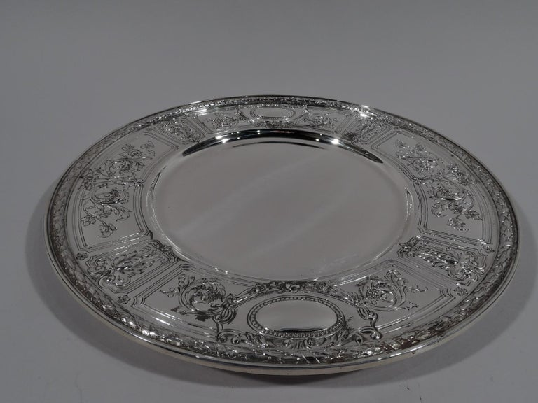 Set of 6 Maintenon sterling silver dinner plates. Made by Gorham in Providence in 1928. Each: Deep and plain well. Wide shoulder with chased leafy-scrollwork and flowers spilling over curvilinear frames. Two beaded oval frames (vacant). Imbricated