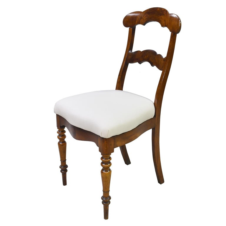 A set of 6 Biedermeier dining chairs in West Indies mahogany with upholstered slip seat. Back is high & has two cross rails with scrolled arches featuring a beautiful crotch mahogany. Seat has a serpentine front and sides with inverted arches on the