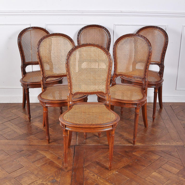 A set of six, late 19th century, Louis XVI-style chairs with cane seats and backs. The curved backs are particularly well-carved, with a fine ribbon motif along their edges; the seats are similarly rounded and raised on elegant turned and fluted