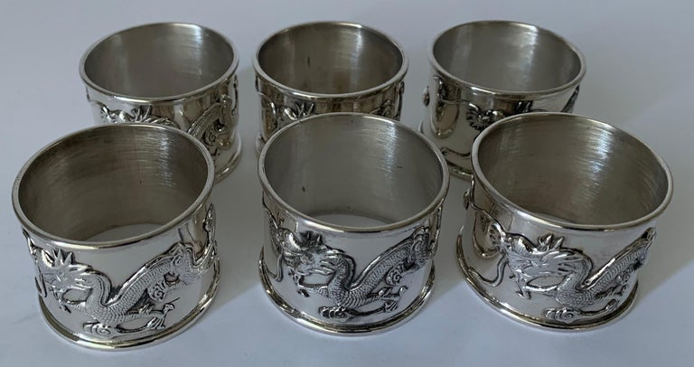 Set of 6 silver plate Chinese export napkin rings. Raised overall dragon motif. Newly re-plated and polished to a high shine. No makers mark or signature.