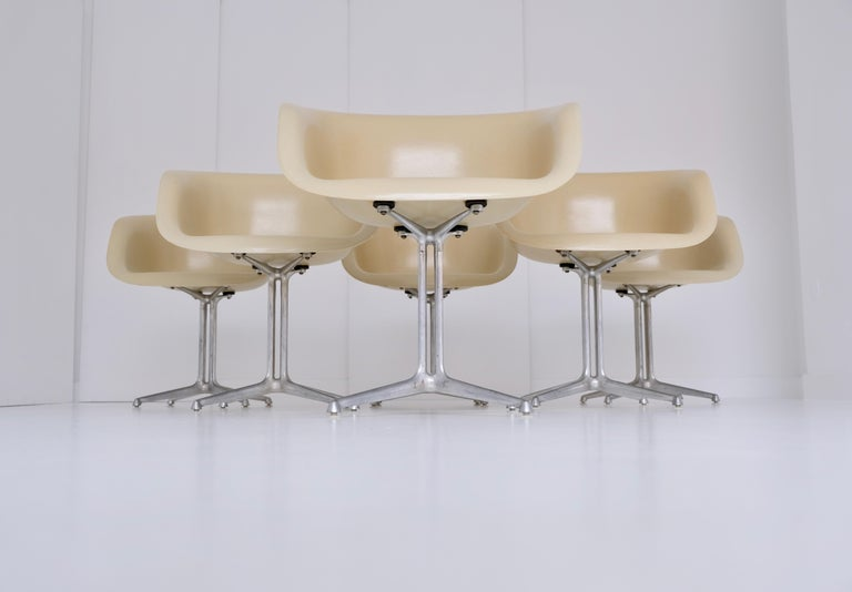 A set of six dining height armchairs (dal, model 1730-1) with parchment colored fiberglass shell seats and solid cast aluminum four-star pedestal base in 'la fonda' design.