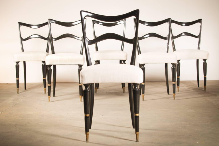 Beautifully shaped set of six ebonized mahogany dining room chairs attributed to Osvaldo Borsani. Completely redone, cleaned, waxed and reupholstered in the best quality new foam and off white / cream fabric. The matching dining table is available